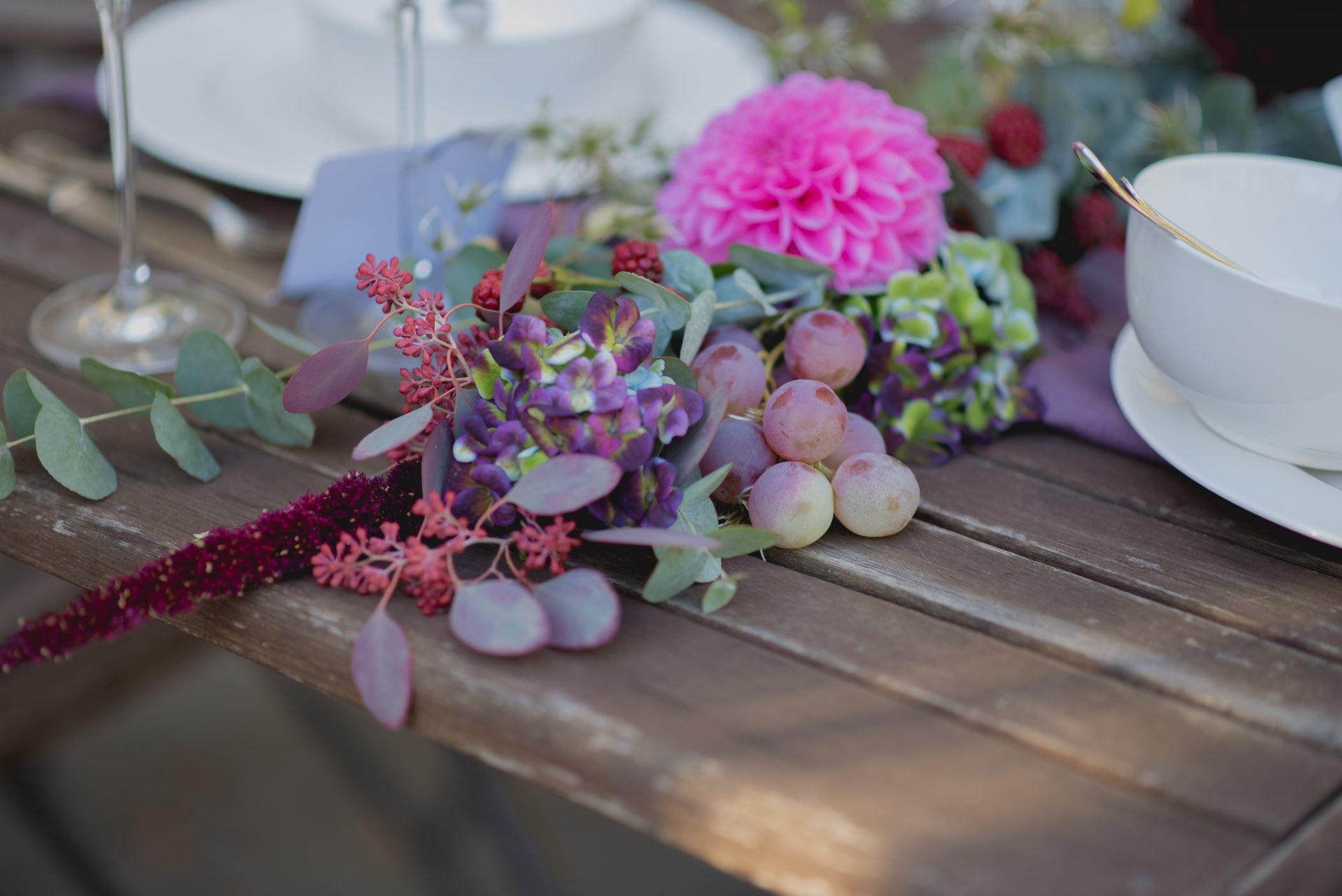 Hochzeitsdekoration mit Früchten und Blüten in herbstlichen Farben.
